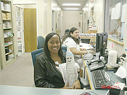 Regina Marsh (holding Nevi) and Gloria Alvarez welcome their unusual visitor to the Dental Care Center office.